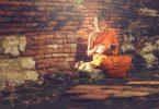 Menino budista sentado lendo um livro.