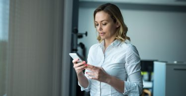 Attractive businesswoman texting with clients on a mobile phone.