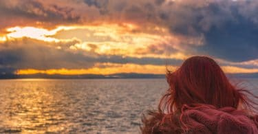Redhead woman at sunset - Landscape with a colorful sunset over the Bodensee lake and a red haired woman admiring the horizon in Friedrichshafen Germany.