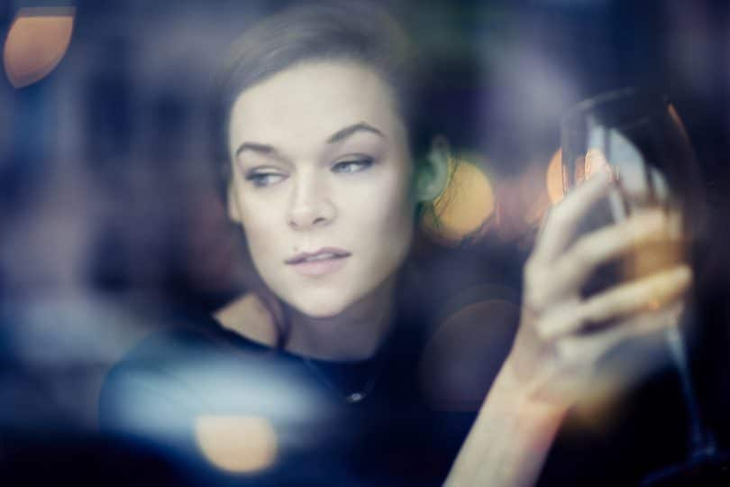 Young woman close-up portrait through window in a restaurant. leisure time with red wine