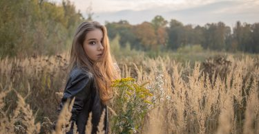 sad girl walking in dry grass in autumn nature looking back