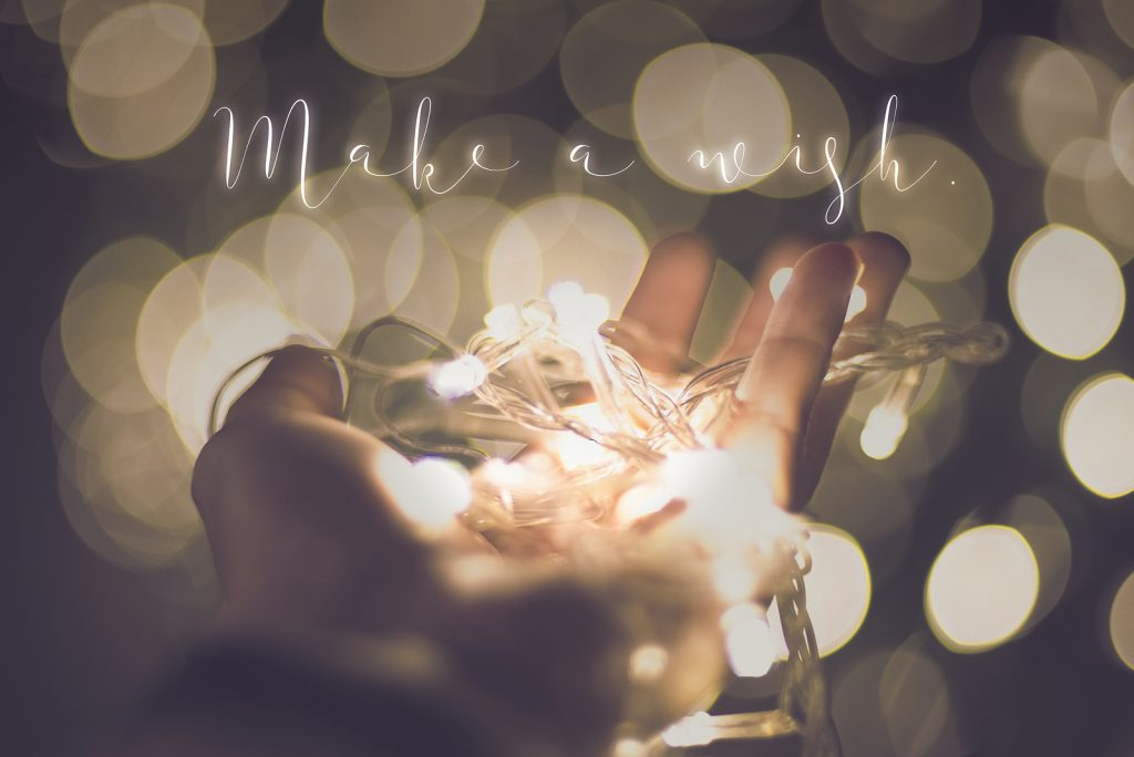 Make a wish word over hand with light bokeh in vintage filter,Holiday quote,christmas season.