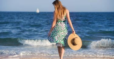 Young barefoot woman with hat walking on ocean beach at sunny hot day and enjoy the vacation. Girl wearing summer dress walking on sand.