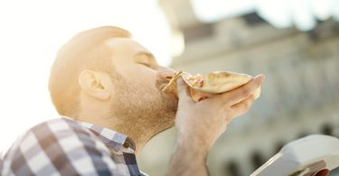 Man eating pizza snack outdoors.Handsome young man eating a slice of pizza outside on the street.