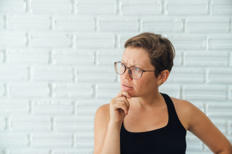 Young attractive girl with glasses and a freelancer c short hair do makes thoughtful face. Thoughts, ideas.