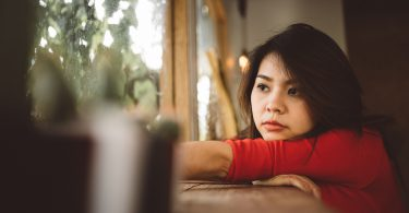 Portrait of lonely young Asian woman looking through a window.
