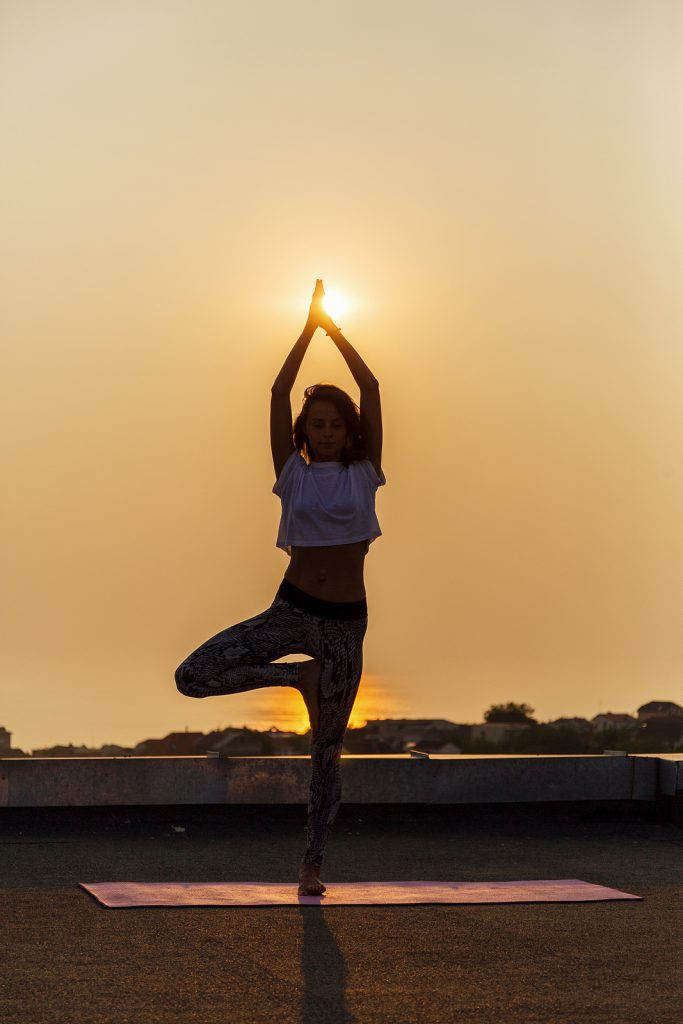Young woman practicing yoga on the roof