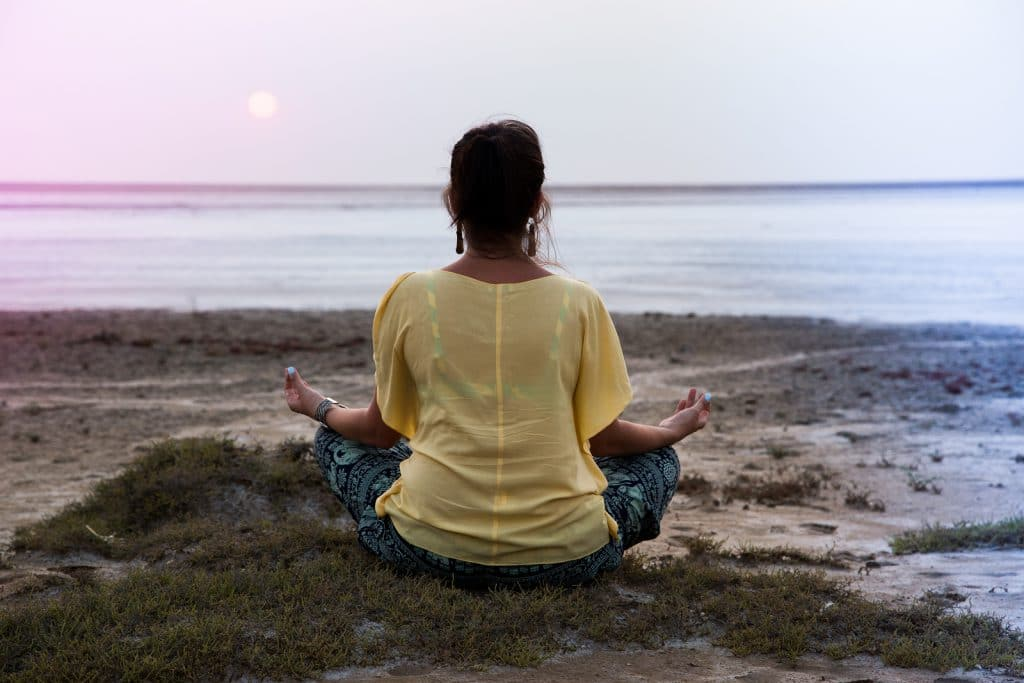 girl meditating at sunset. sits back looks at the sun.