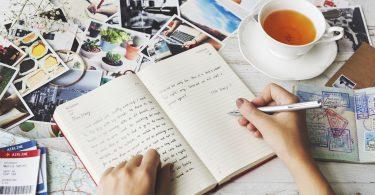 Hands Writing Travel Journal Tea Concept