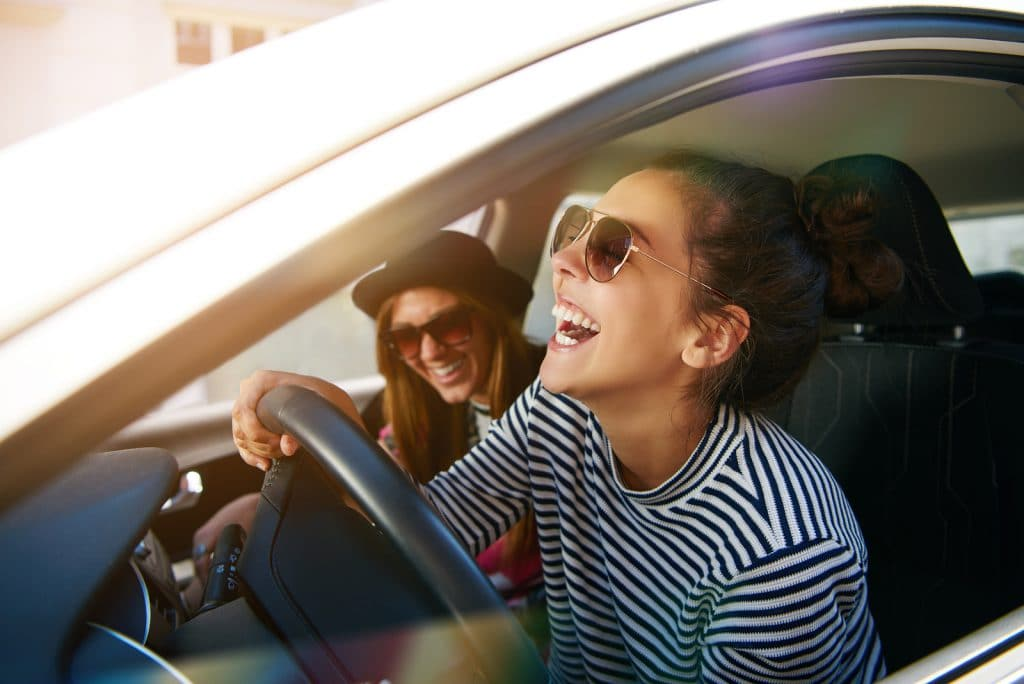 Laughing young woman wearing sunglasses driving a car with her girl friend close up profile view through the open window