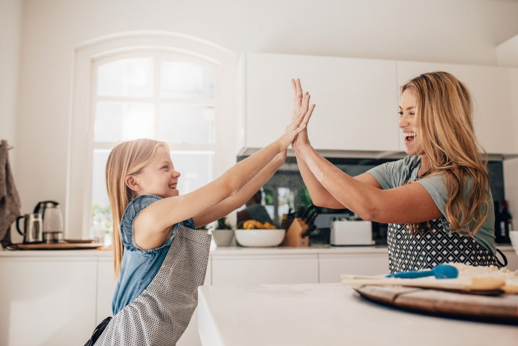 Little girl and her mother in kitchen giving high five. Mother and daughter in kitchen cooking.