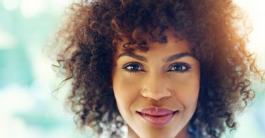 Portrait of stunning afro-american woman with curly hair smiling at camera on blurred outside background.