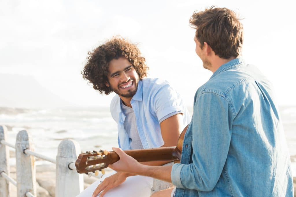 Rear view of young man playing guitar sitting on fence at beach with friend. Smiling guy listening his friend playing acustic guitar at sunset.