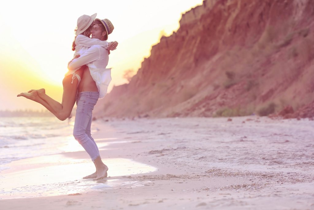 Young happy couple on beach on cliff background