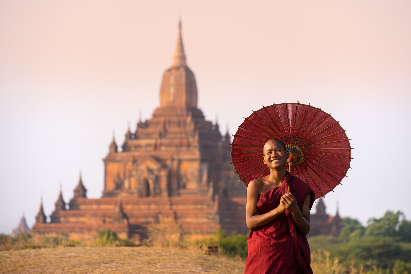 Monge sorrindo e ao seu fundo um templo