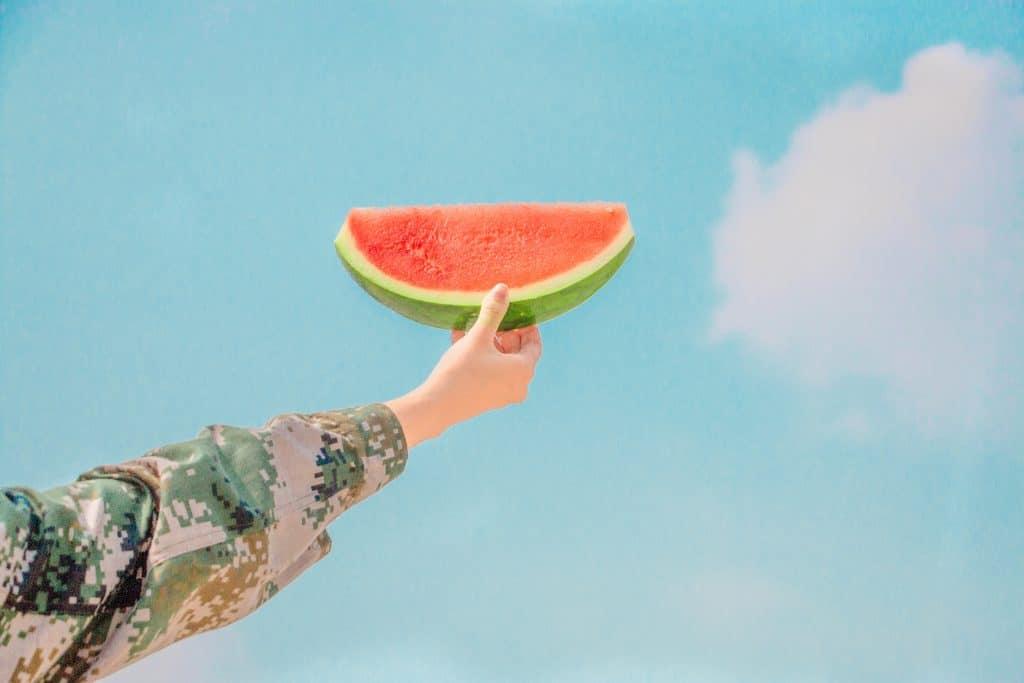 Pessoa segurando uma fatia de melancia. Ao fundo está o céu azul.