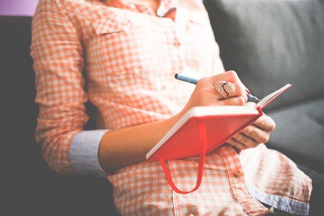 Mulher sentada em um sofá, usando um anel grande na mão direita e escrevendo com uma caneta em um pequeno caderno vermelho.