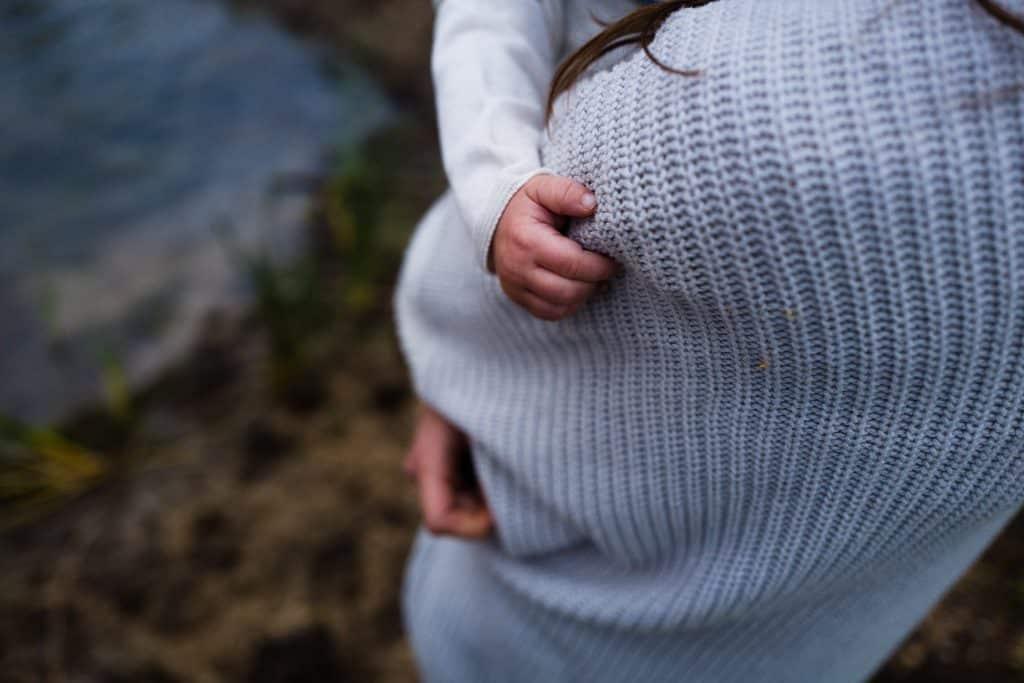 Bebê segurando braço de sua mãe