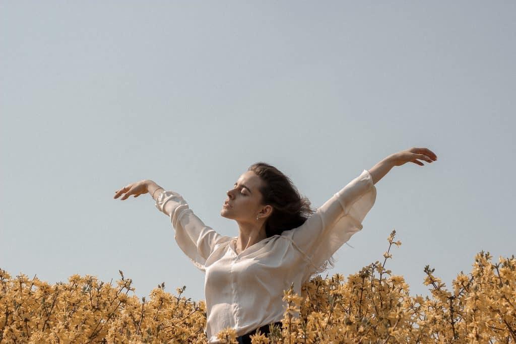 Mulher entre flores com os braços levantados
