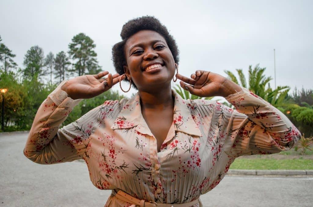 Mulher de braços abertos sorrindo ao ar livre.