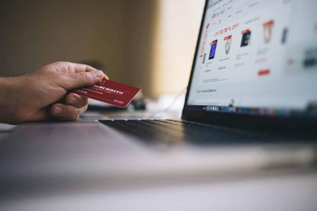 Pessoa segurando cartão de crédito ao lado do computador