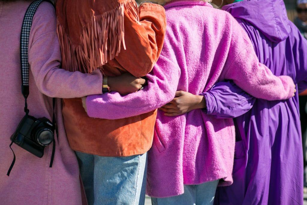 Foto das costas de quatro pessoas que estão abraçadas.