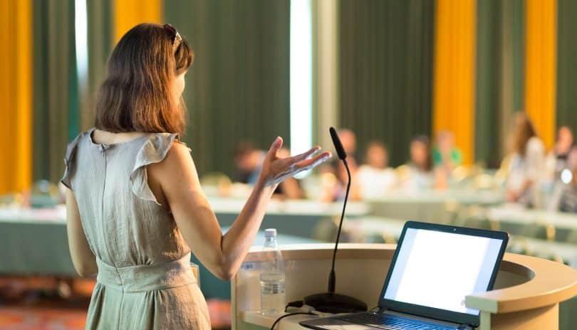 Mulher branca de cabelos curtos num auditório, enquanto realiza um discurso.