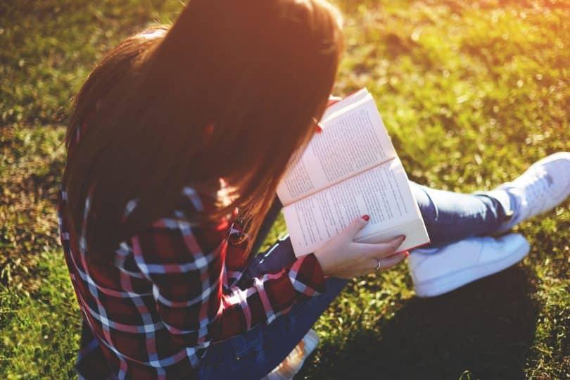 Mulher sentada na grama lendo livro.