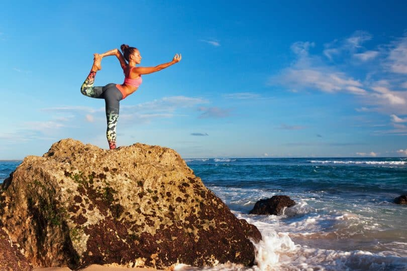 Mulher faz yoga sobre rocha.
