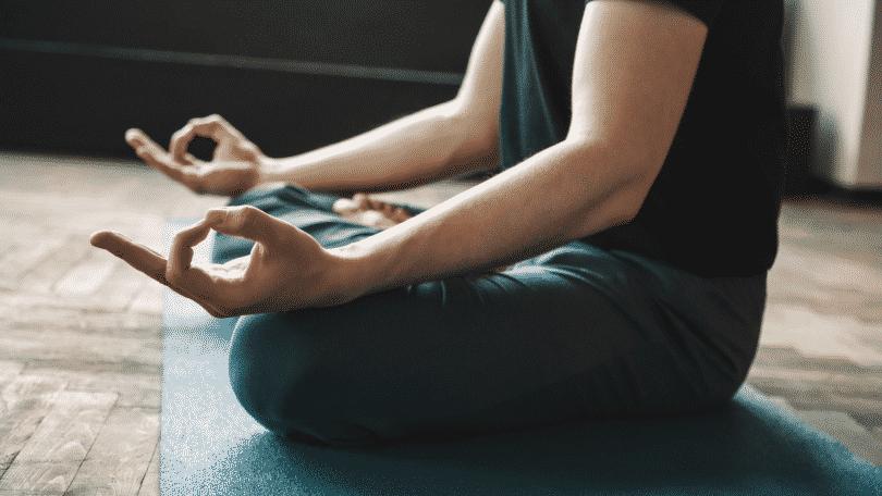 Pessoa sentada fazendo posição de yoga