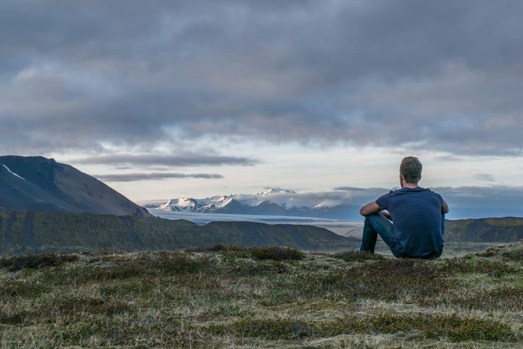 Homem sentado em um espaço aberto olhando para o horizonte.