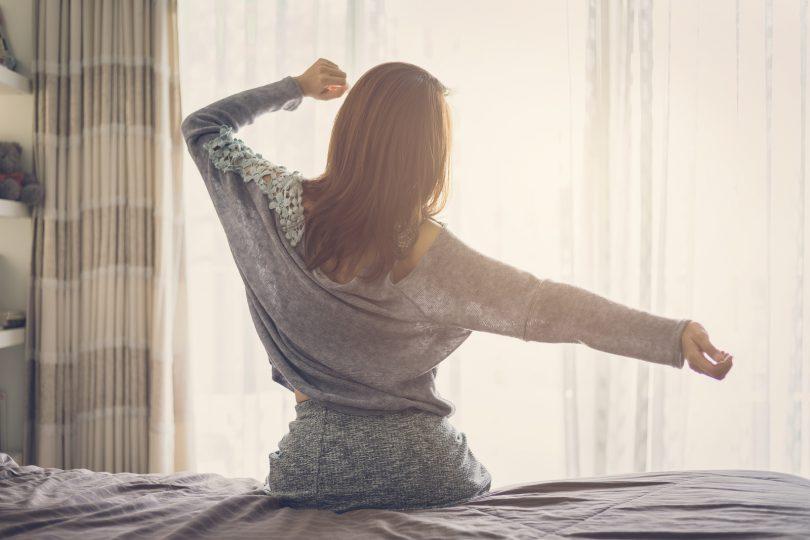 Mulher sentada em cama esticando os braços como se estivesse se espreguiçando.