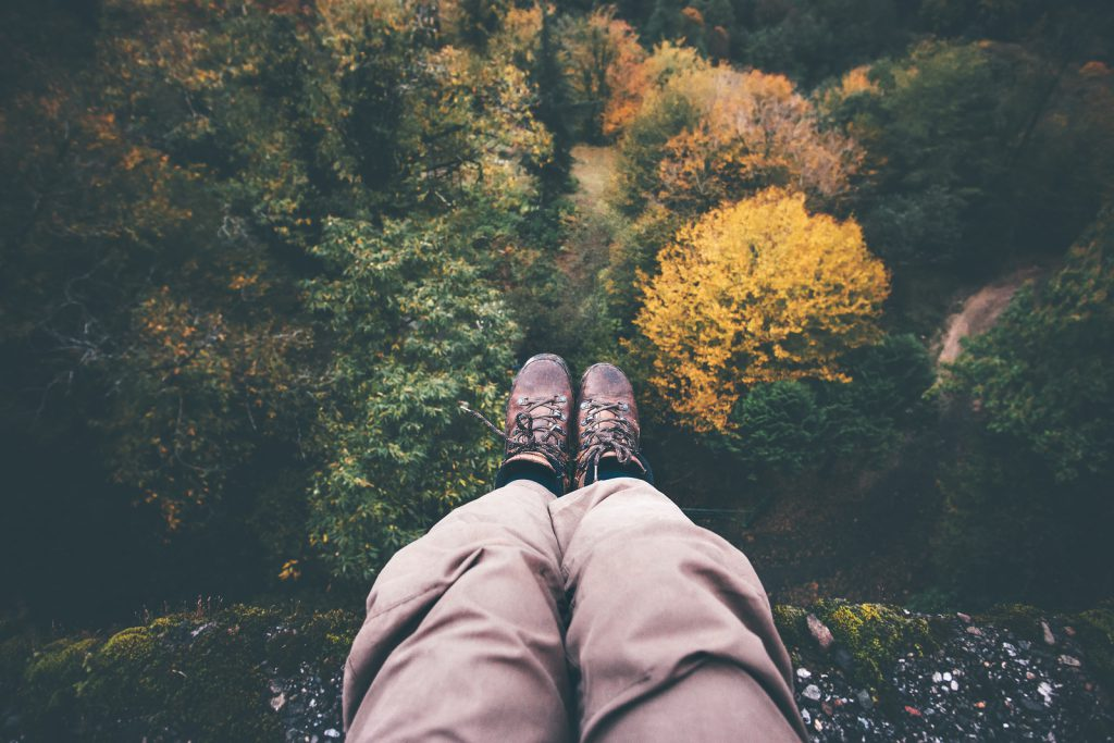Feet selfie on cliff with forest aerial view Travel Lifestyle adventure vacations concept into the wild