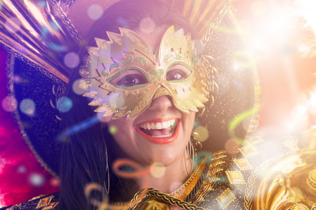 Mulher com máscara de carnaval sorrindo.