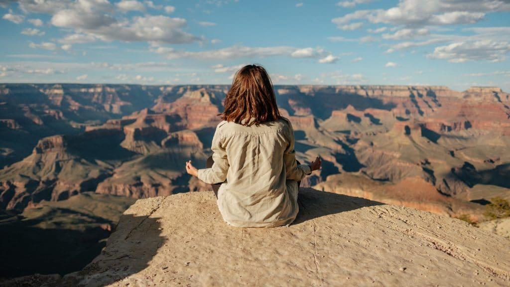 Mulher sentada em uma montanha em posição de meditação. À sua frente está a paisagem de um vale montanhoso.