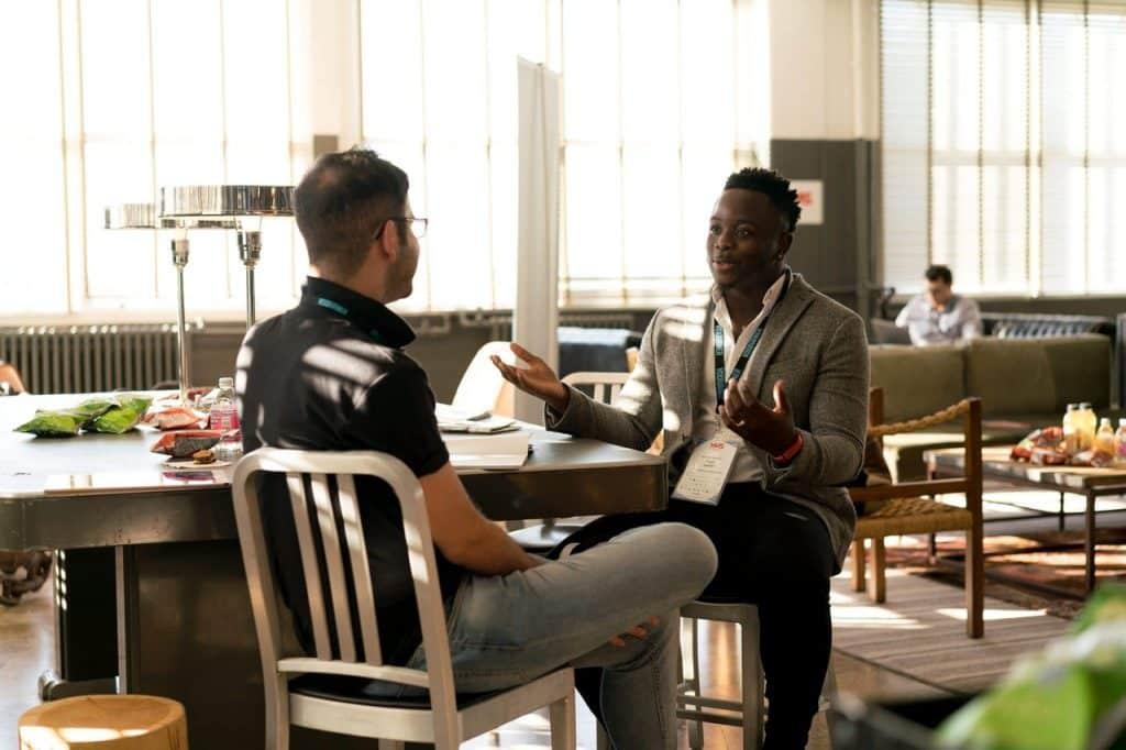Dois homens sentados na cadeira conversando.
