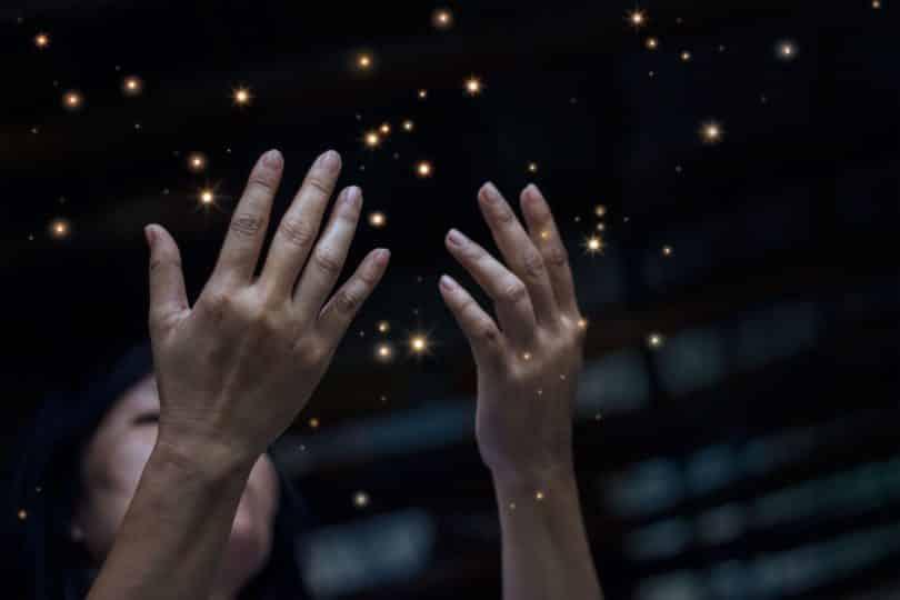 Mulher com as mãos para cima em meio as estrelas do céu