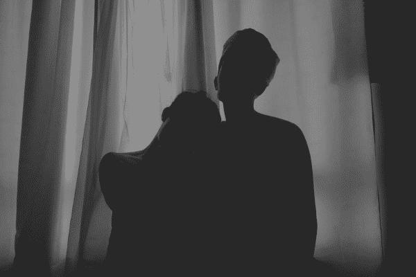 Silhueta de um casal em frente de cortinas da janela em um quarto escuro