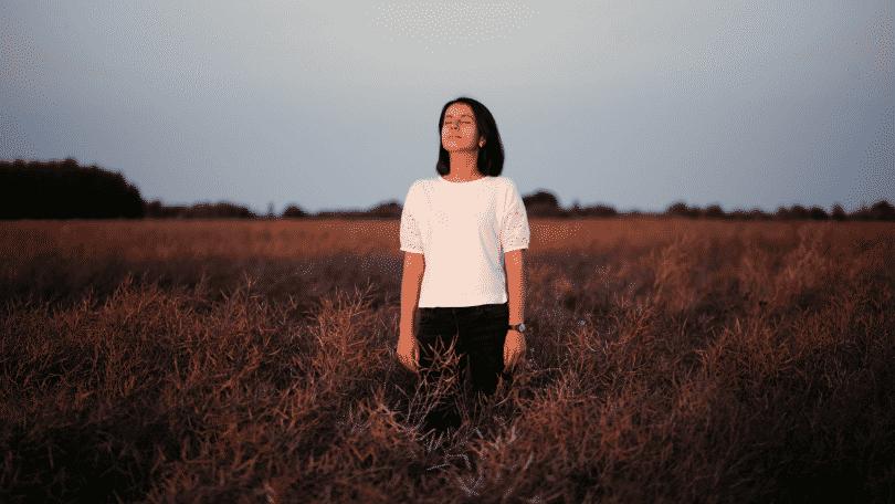 Mulher de olhos fechados, parada em um campo aberto