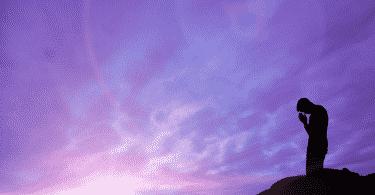 Foto de um homem orando no alto de uma montanha