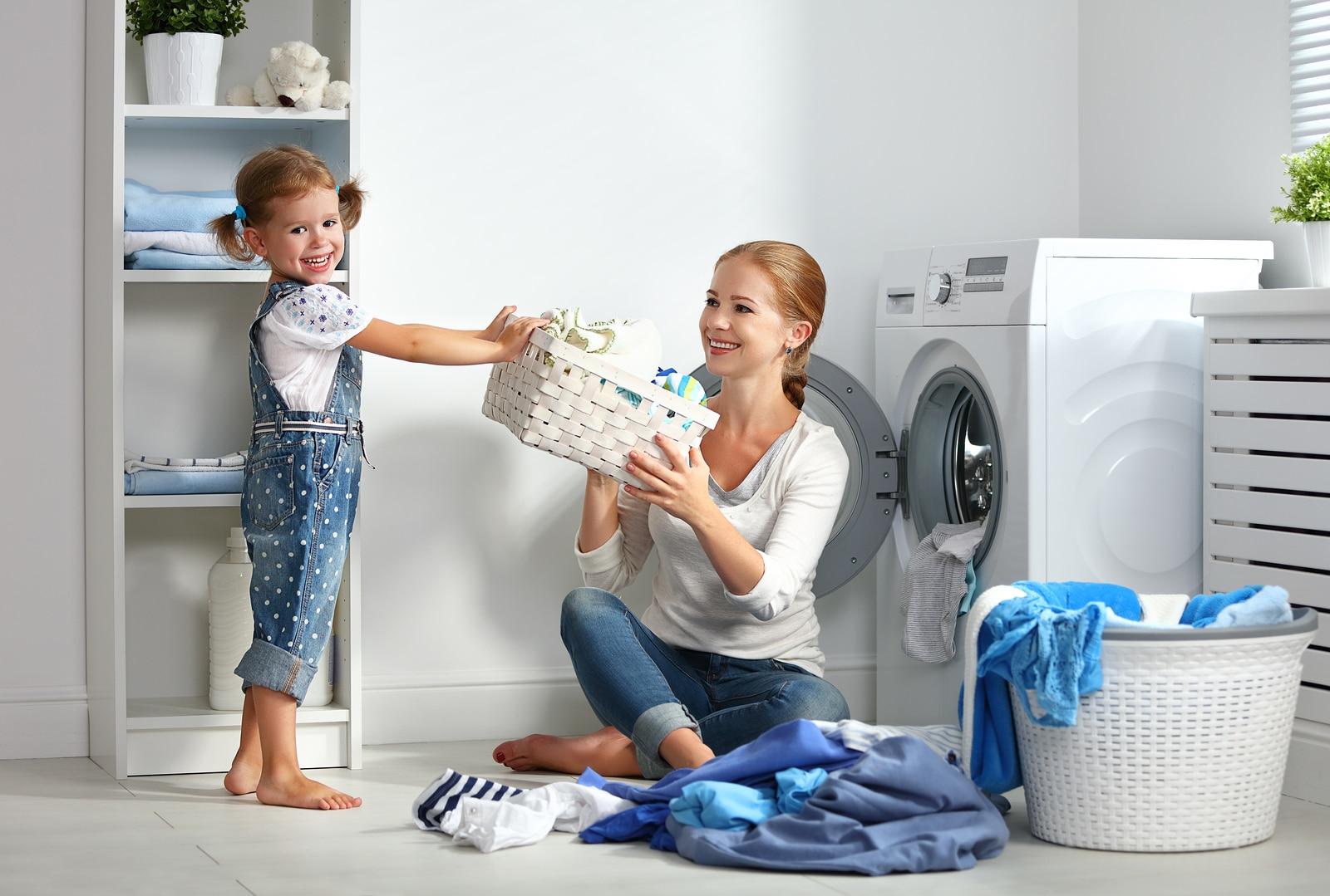 Menina sorrindo com a sua mãe na lavanderia da casa.