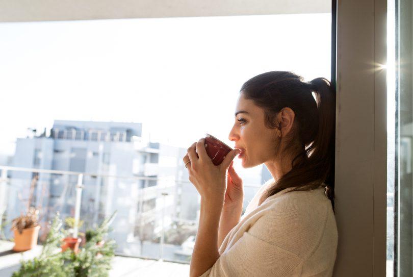 Mulher na janela tomando uma xícara de chá