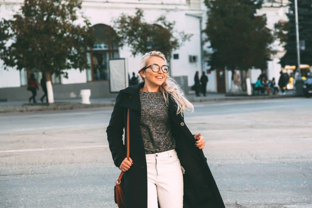 Mulher em pé, sorrindo. Ela está com uma calça branca, uma blusa cinza e um sobretudo preto.