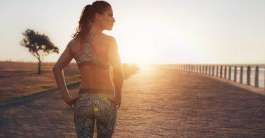 Mulher com roupa de ginástica em calçadão à beira-mar, com o sol no horizonte.