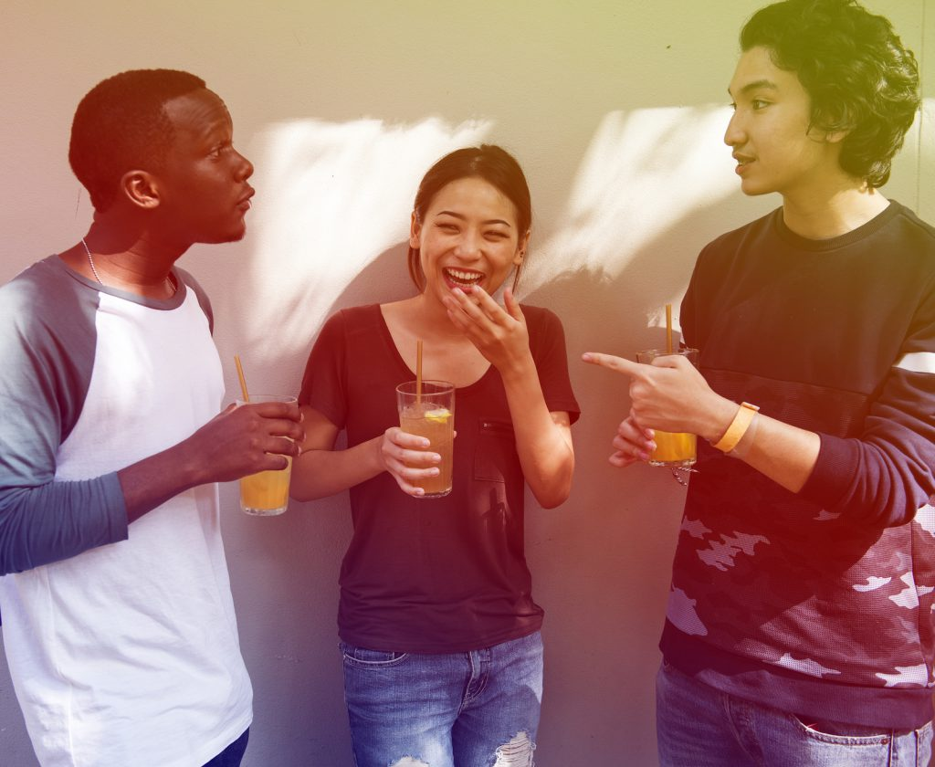 Três amigos conversando. Eles estão com copos de sucos na mão e estão sorrindo.