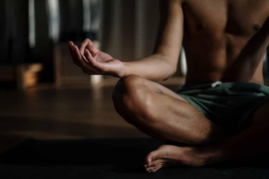 Homem meditando sentado no chão