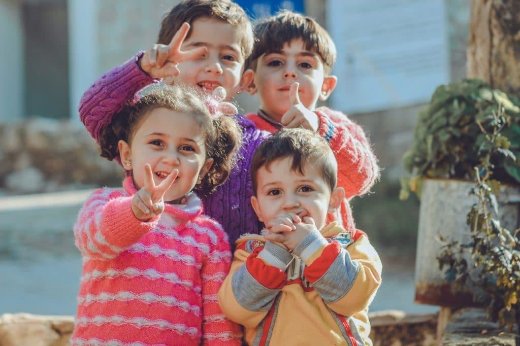 Três meninos e uma menina, com blusas de inverno, sorrindo para a câmera e fazendo gestos com as mãos.
