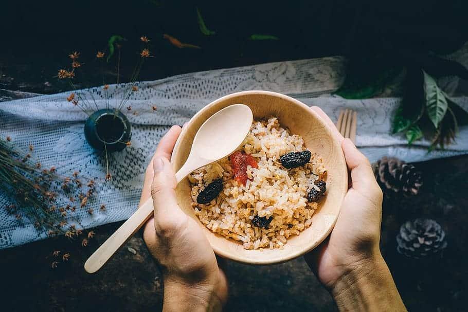 Mãos segurando tigela com arroz integral e carnes secas, e uma colher.