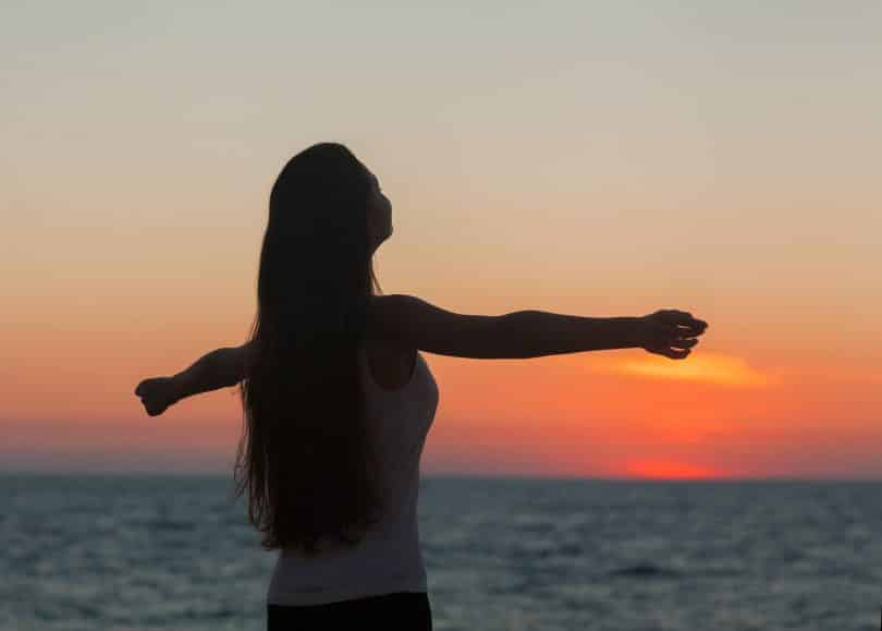Mulher de braços abertos sob o pôr do sol na praia.