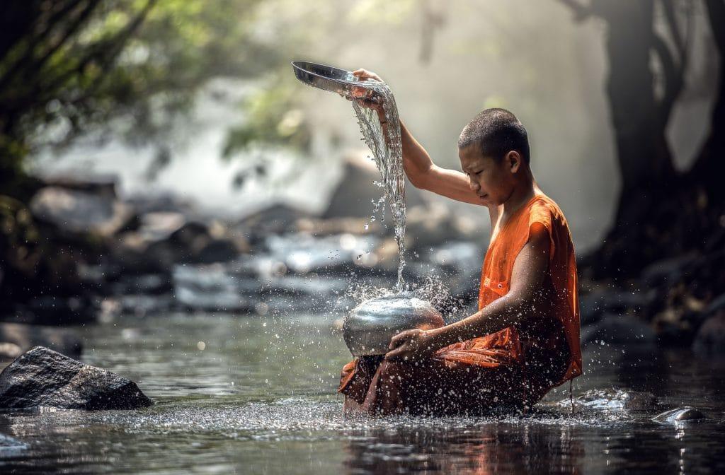 Jovem monge em um lago